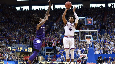 Jan 13, 2018; Lawrence, KS, USA; Kansas Jayhawks guard Devonte' Graham (4) shoots scores a three point basket as Kansas State Wildcats guard Cartier Diarra (2) defends during the second half at Allen Fieldhouse. Mandatory Credit: Denny Medley-USA TODAY Sports