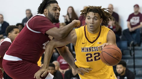 FILE - In this Friday, Nov. 24, 2017 file photo, Minnesota center Reggie Lynch (22) drives to the basket against UMass center Rashaan Holloway during the first half of an NCAA college basketball game in New York. Minnesota basketball player Reggie Lynch has been recommended for expulsion following a newly public allegation of sexual assault. The Star Tribune and the St. Paul Pioneer Press report the university's Equal Opportunity and Affirmative Action office found Lynch responsible for sexual misconduct in an alleged assault April 7, 2016. Both newspapers say they obtained a Jan. 3, 2018 finding by the office. (AP Photo/Mary Altaffer, File)