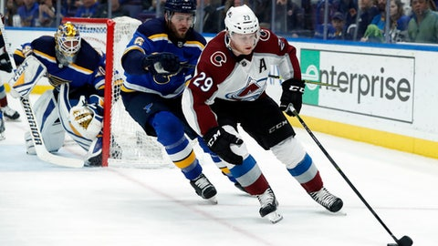 Colorado Avalanche's Nathan MacKinnon, right, controls the puck as St. Louis Blues' Joel Edmundson, center, and goaltender Carter Hutton defend during the third period of an NHL hockey game Thursday, Jan. 25, 2018, in St. Louis. The Blues won 3-1. (AP Photo/Jeff Roberson)