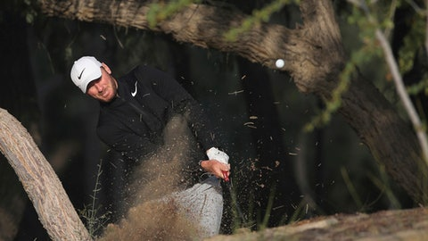 England's Chris Wood plays a shot on the dirt of the 13th hole during the second round, which was delayed due to fog yesterday, of the Dubai Desert Classic golf tournament in Dubai, United Arab Emirates, Saturday, Jan. 27, 2018. (AP Photo/Kamran Jebreili)