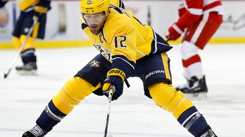 FILE - In this Oct. 21, 2016, file photo, Nashville Predators center Mike Fisher (12) reaches for the puck against Detroit Red Wings in the first period of an NHL hockey game in Detroit. Predators general manager David Poile announced Wednesday, Jan. 31, 2018, that Fisher is coming out of retirement to make a comeback and play once more. The team hopes to sign a contract around the Feb. 26 trade deadline.  (AP Photo/Paul Sancya, File)