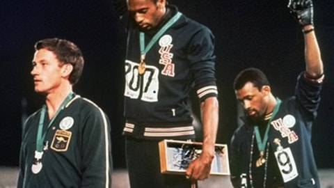 FILE - In this Oct. 16, 1968, file photo, extending gloved hands skyward in racial protest, U.S. athletes Tommie Smith, center, and John Carlos stare downward during the playing of national anthem after Smith received the gold and Carlos the bronze for the 200 meter run at the Summer Olympic Games in Mexico City. Australian silver medalist Peter Norman is at left. (AP Photo, File)