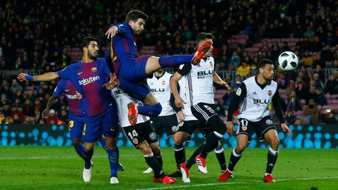 FC Barcelona's Gerard Pique, center, kicks the ball during the Spanish Copa del Rey, semifinal, first leg, soccer match between FC Barcelona and Valencia at the Camp Nou stadium in Barcelona, Spain, Thursday, Feb. 1, 2018. (AP Photo/Manu Fernandez)