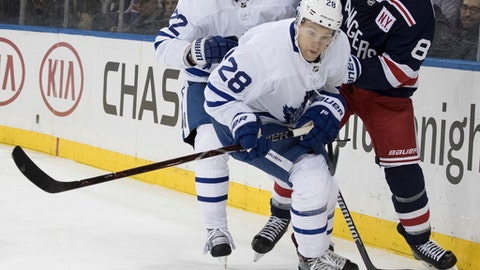 Toronto Maple Leafs right wing Connor Brown (28) and defenseman Nikita Zaitsev (22) battle for the puck against New York Rangers left wing Cody McLeod (8) during the second period of an NHL hockey game, Thursday, Feb. 1, 2018, at Madison Square Garden in New York. (AP Photo/Mary Altaffer)