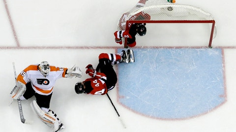 Philadelphia Flyers goalie Alex Lyon, left, tries to keep his balance after colliding with New Jersey Devils right wing Kyle Palmieri, right, and left wing Miles Wood (44) during the second period of an NHL hockey game, Thursday, Feb. 1, 2018, in Newark, N.J. (AP Photo/Julio Cortez)