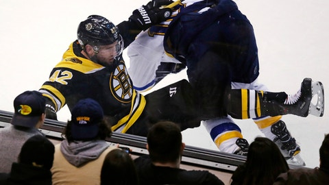 Boston Bruins right wing David Backes (42) is dropped to the ice on a hard check by St. Louis Blues center Brayden Schenn during the third period of an NHL hockey game in Boston, Thursday, Feb. 1, 2018. The Bruins defeated the Blues 3-1. (AP Photo/Charles Krupa)