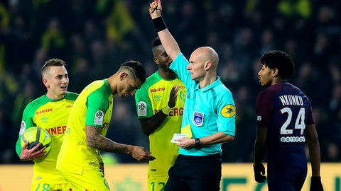 FILE - In this Jan.14 2018 file photo, French referee Tony Chapron gives a red card to Nantes defender Diego Carlos, second left, after Carlos inadvertently clipped the referee's heels during the French League One soccer match between Nantes and Paris Saint Germain, in Nantes, western France. The French soccer federation has banned referee Tony Chapron for three months after he kicked a player during a league match. (AP Photo/David Vincent, File)