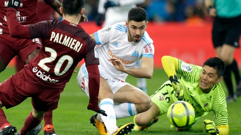 Marseille's Morgan Sanson, center, scores despite Metz's goalkepper Eiji Kawashima, right, and Metz's Julian Palmieri, during the League One soccer match between Marseille and Metz, at the Velodrome Stadium, in Marseille, southern France, Friday, Feb. 2, 2018. (AP Photo/Claude Paris)
