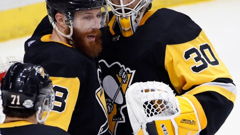 Pittsburgh Penguins goaltender Matt Murray (30) celebrates with Ian Cole (28) as Evgeni Malkin (71) approaches, after getting a 7-4 win over the Washington Capitals in an NHL hockey game in Pittsburgh, Friday, Feb. 2, 2018. (AP Photo/Gene J. Puskar)