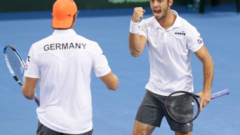 Tim Puetz of Germany, right, reacts with his team mate Jan-Lennard Struff ,left, after winning a point in the doubles match between Germany and Australia at the Davis Cup World Group first round in Brisbane, Australia, Saturday, Feb.3, 2018. (AP Photo/Tertius Pickard)