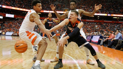 Virginia's Kyle Guy, center, passes the ball around Matthew Moyer, left, and Oshae Brissett, right, in the second half of an NCAA college basketball game in Syracuse, N.Y., Saturday, Feb. 3, 2018. Virginia won 59-44. (AP Photo/Nick Lisi)