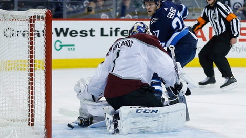 a breakaway shot by Winnipeg Jets' Nikolaj Ehlers' (27) trickles through the pads of Colorado Avalanche's goaltender Semyon Varlamov (1), but hits the post during the second period of an NHL hockey game Saturday, Feb. 3, 2018, in Winnipeg, Manitoba. (John Woods/The Canadian Press via AP)