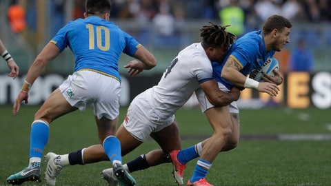 England's Anthony Watson, centre tackles Italy's Matteo Minozz, right, during the Six Nations rugby union international match between Italy and England at the Olympic Stadium, in Rome, Italy, Sunday, Feb. 4, 2018. (AP Photo/Gregorio Borgia)