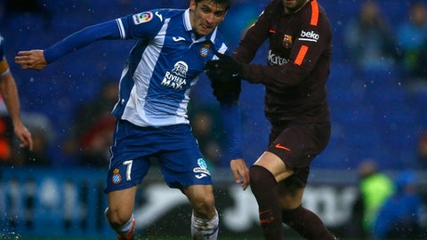 FC Barcelona's Gerard Pique, right, duels for the ball against Espanyol's Gerard Moreno during the Spanish La Liga soccer match between Espanyol and FC Barcelona at RCDE stadium in Cornella Llobregat, Spain, Sunday, Feb. 4, 2018. (AP Photo/Manu Fernandez)