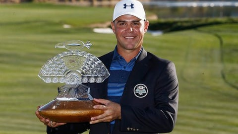 Gary Woodland smiles for photographers with the championship trophy after his one-hole playoff win after the final round of the Waste Management Phoenix Open golf tournament Sunday, Feb. 4, 2018, in Scottsdale, Ariz. (AP Photo/Ross D. Franklin)