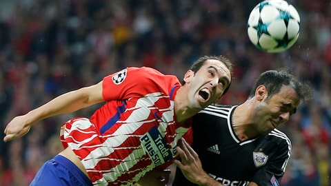 FILE - In this Tuesday, Oct. 31, 2017 file photo, Atletico's Diego Godin, left, and Qarabag's Elvin Ismayilov jump for the ball during a Group C Champions League soccer match between Atletico Madrid and Qarabag at the Metropolitano stadium in Madrid, Spain. Atletico Madrid says defender Diego Godin has undergone reconstructive procedure on his mouth after losing some of his teeth in a brutal collision in a Spanish league match Sunday Feb. 4, 2018. (AP Photo/Paul White, File)