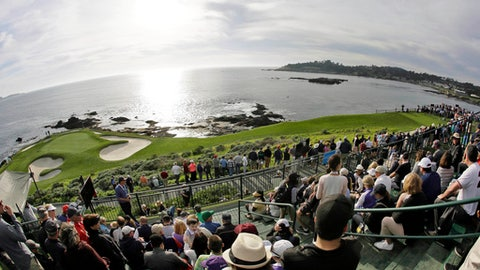 FILE - In this Feb. 10, 2016, file photo taken with a fisheye lens, fans line the seventh hole of the Pebble Beach Golf Links to watch the inaugural $1 million celebrity hole-in-one event of the AT&T Pebble Beach National Pro-Am golf tournament in Pebble Beach, Calif. The AT&T Pebble Beach Pro-Am is a confluence of some of the most important elements on the PGA Tour, from corporate to entertainment, from professionals to amateurs.  (AP Photo/Eric Risberg, File)