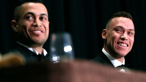 This Jan. 28, 2018 photo shows National League Most Valuable Player Giancarlo Stanton, left, and American League Rookie of the Year Aaron Judge sitting side-by-side during the New York Chapter of the Baseball Writers' Association of America annual dinner in New York where both men picked up their awards. The New York Yankees will open the gates three hours before spring training home games, allowing fans to watch Aaron Judge and new teammate Giancarlo Stanton take their thwacks during batting practice. (AP Photo/Kathy Willens)
