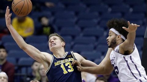 Michigan forward Moritz Wagner, left, reaches for a rebound next to Northwestern center Barret Benson during the first half of an NCAA college basketball game Tuesday, Feb. 6, 2018, in Rosemont, Ill. (AP Photo/Nam Y. Huh)