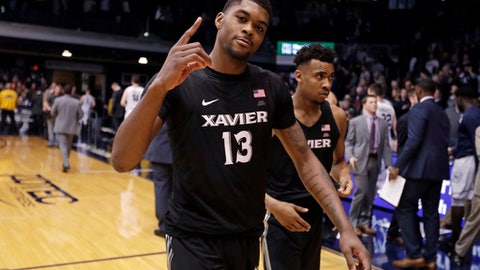 Xavier forward Naji Marshall (13) and guard Paul Scruggs (1) walk off the court following the team's 98-93 overtime win against Butler in an NCAA college basketball game in Indianapolis, Tuesday, Feb. 6, 2018. (AP Photo/Michael Conroy)