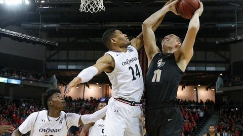 Cincinnati's Kyle Washington (24) blocks a shot by Central Florida's Rokas Ulvydas (11) in the second half of an NCAA college basketball game, Tuesday, Feb. 6, 2018, in Highland Heights, Ky. Cincinnati won 77-40. (AP Photo/John Minchillo)