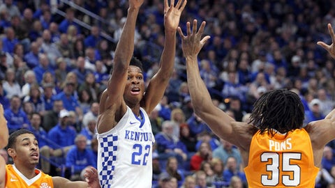 Kentucky's Shai Gilgeous-Alexander (22) passes away from the defense of Tennessee's James Daniel III (3) and Yves Pons (35) during the first half of an NCAA college basketball game, Tuesday, Feb. 6, 2018, in Lexington, Ky. (AP Photo/James Crisp)