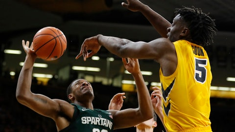 Iowa forward Tyler Cook blocks a shot by Michigan State forward Xavier Tillman (23) during the first half of an NCAA college basketball game Tuesday, Feb. 6, 2018, in Iowa City, Iowa.(AP Photo/Charlie Neibergall)