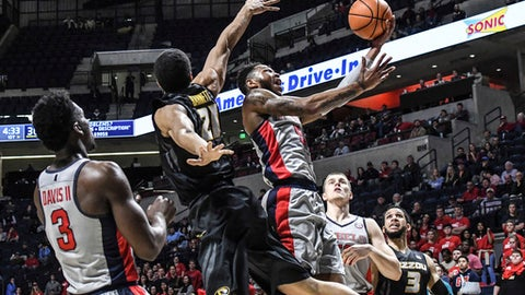 Mississippi's Markel Crawford (5) scores and is fouled by Missouri's Jordan Barnett (21) as Mississippi's Terence Davis II (3), Justas Furmanavicius (50) and Missouri's Kassius Robertson (3) look on during an NCAA college basketball game in Oxford, Miss., Tuesday, Feb. 6, 2018. (Bruce Newman/The Oxford Eagle via AP)