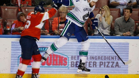 Florida Panthers center Micheal Haley, left, slams Vancouver Canucks defenseman Erik Gudbranson (44) into the boards during the second period of an NHL hockey game Tuesday, Feb. 6, 2018, in Sunrise, Fla. The Panthers defeated the Canucks 3-1. (AP Photo/Wilfredo Lee)