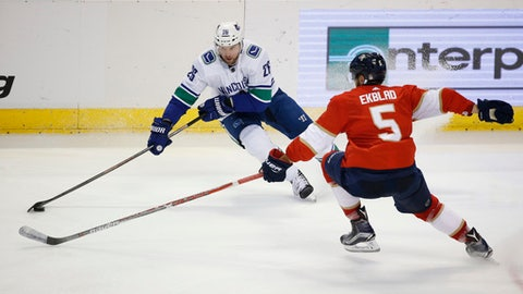 Vancouver Canucks left wing Thomas Vanek (26) and Florida Panthers defenseman Aaron Ekblad (5) vie for the puck during the third period of an NHL hockey game Tuesday, Feb. 6, 2018, in Sunrise, Fla. The Panthers defeated the Canucks 3-1. (AP Photo/Wilfredo Lee)