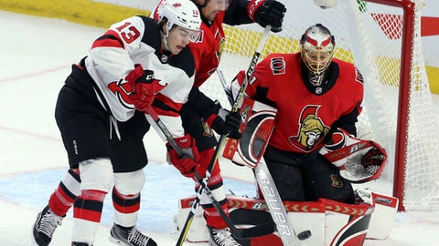 Ottawa Senators' Cody Ceci ties up New Jersey Devils' Nico Hischier (13) as Senator goaltender Craig Anderson watches the puck during the third period of an NHL hockey game Tuesday, Feb. 6, 2018, in Ottawa, Ontario. (Fred Chartrand/The Canadian Press via AP)