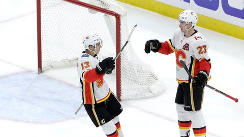 Calgary Flames' Sean Monahan (23) celebrates his goal with Johnny Gaudreau during the third period of an NHL hockey game against the Chicago Blackhawks on Tuesday, Feb. 6, 2018, in Chicago. The Flames won 3-2. (AP Photo/Charles Rex Arbogast)