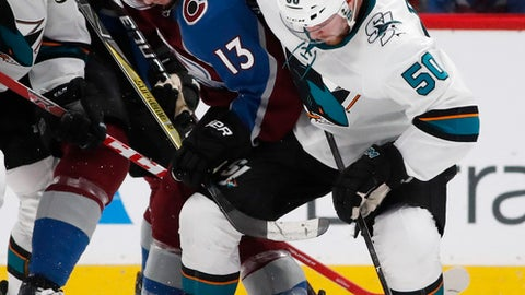 Colorado Avalanche center Alexander Kerfoot, left, fights for control of the puck with San Jose Sharks center Chris Tierney during the third period of an NHL hockey game Tuesday, Feb. 6, 2018, in Denver. The Avalanche won 3-1. (AP Photo/David Zalubowski)
