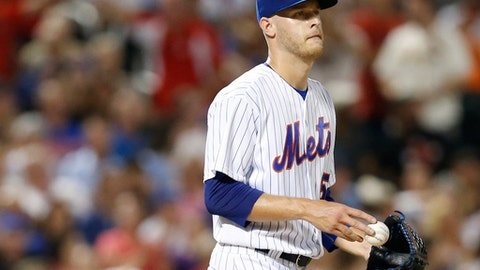 FILE - In this July 17, 2017, file photo, New York Mets starting pitcher Zack Wheeler looks toward the giant video screen in centerfield after allowing a two-run home run to St. Louis Cardinals' Paul DeJong in the allowing a sixth inning of a baseball game in New York. Wheeler went to salary arbitration with the Mets after struggling in his return from Tommy John surgery. Wheeler asked for a raise from $800,000 to $1.9 million, and the Mets argued he should be paid $1.5 million. A decision by arbitrators John Skonier, Andrew Strongin and Phillip LaPorte is expected Thursday, Feb. 8, 2018.  (AP Photo/Kathy Willens, File)