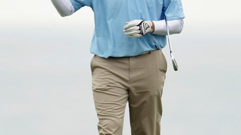 Dallas Cowboys quarterback Tony Romo waves after hitting to the eighth green at Pebble Beach Golf Links during the final round of the AT&T Pebble Beach National Pro-Am golf tournament in Pebble Beach, Calif., Sunday, Feb. 12, 2012. (AP Photo/Eric Risberg)