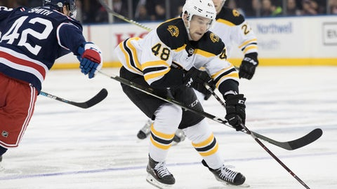 Boston Bruins defenseman Matt Grzelcyk (48) controls the puck as New York Rangers' Brendan Smith (42) defends during the third period of an NHL hockey game Wednesday, Feb. 7, 2018, at Madison Square Garden in New York. The Bruins won 6-1. (AP Photo/Mary Altaffer)