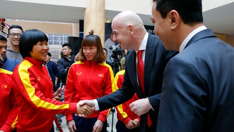 FIFA President Gianni Infantino, center, shakes hands with a Vietnamese female football player in Hanoi, Vietnam, Thursday, Feb. 8, 2018. Infantino is on one-day visit to the Southeast Asian country to boost cooperation between the world football body and Vietnam. (AP Photo/Tran Van Minh)