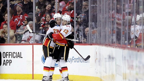 Calgary Flames left wing Johnny Gaudreau (13) celebrates his goal against the New Jersey Devils with teammate Sean Monahan (23) during the second period of an NHL hockey game, Thursday, Feb. 8, 2018, in Newark, N.J. (AP Photo/Julio Cortez)