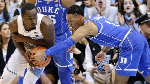 North Carolina's Theo Pinson controls the ball while Duke's Trevon Duval reaches in during the first half of an NCAA college basketball game in Chapel Hill, N.C., Thursday, Feb. 8, 2018. (AP Photo/Gerry Broome)