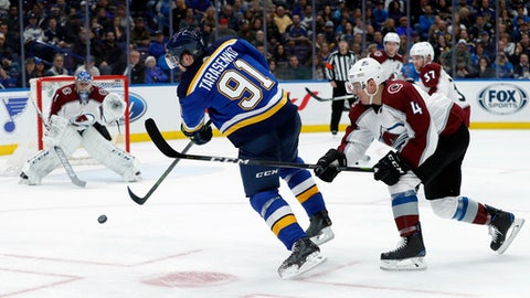 St. Louis Blues' Vladimir Tarasenko, of Russia, takes a shot as Colorado Avalanche goaltender Semyon Varlamov, left, of Russia, and Tyson Barrie (4) defend during the second period of an NHL hockey game Thursday, Feb. 8, 2018, in St. Louis. (AP Photo/Jeff Roberson)