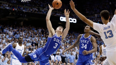 Duke's Grayson Allen (3) drives to the basket while North Carolina's Cameron Johnson (13) defends during the second half of an NCAA college basketball game in Chapel Hill, N.C., Thursday, Feb. 8, 2018. Duke's Wendell Carter Jr. (34) looks on. (AP Photo/Gerry Broome)