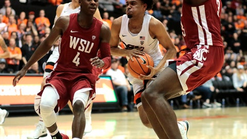 Oregon State's Stephen Thompson Jr., center, drives to the basket past Washington State's Viont'e Daniels (4) and Robert Franks (3) in the first half of an NCAA college basketball game in Corvallis, Ore., Thursday, Feb. 8, 2018. (AP Photo/Timothy J. Gonzalez)