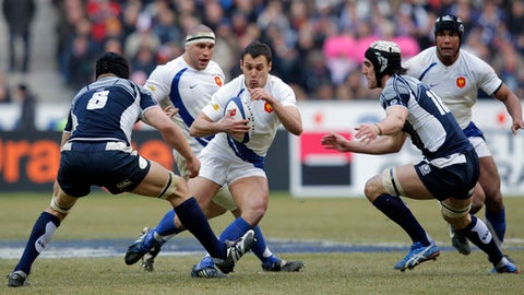 FILE - In this Saturday, Feb. 14, 2009 file photo, France's Lionel Beauxis, center, runs between Scotland's Simon Taylor, left, and Kelly Brown during their Six Nations rugby union international match at the Stade de France in Saint Denis, outside Paris. Lionel Beauxis will start at flyhalf for France against Scotland in Six Nations rugby on Sunday Feb. 11, 2018, six years after his last international cap. (AP Photo/Christophe Ena, File)