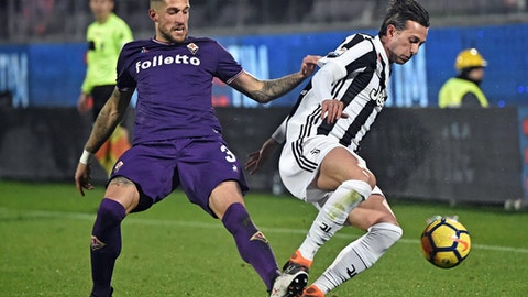 Fiorentina's Cristiano Biraghi and Juventus' Federico Bernardeschi, right, go for the ball during a Serie A soccer match between Fiorentina and Juventus at the Artemio Franchi stadium in Florence, Italy, Friday, Feb. 9, 2018. (Maurizio Degl'Innocenti/ANSA via AP)