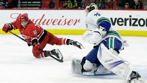 Carolina Hurricanes' Teuvo Teravainen (86), of Finland, tries to score against Vancouver Canucks goalie Jacob Markstrom (25), of Sweden, during the second period of an NHL hockey game in Raleigh, N.C., Friday, Feb. 9, 2018. (AP Photo/Gerry Broome)