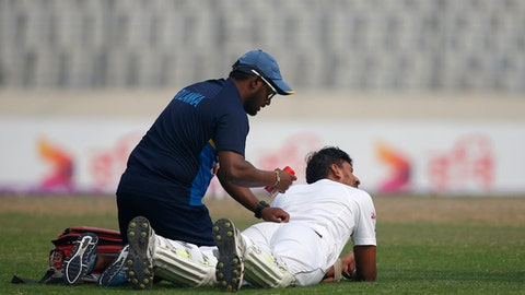 Sri Lanka's team physiotherapist Nirmalan Thanabalasingam attends to Suranga Lakmal, on ground, during the third day of the second and final test cricket match against Bangladesh in Dhaka, Bangladesh, Saturday, Feb. 10, 2018. (AP Photo/A.M. Ahad)