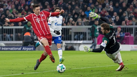 Munich's  Robert Lewandowski, left, scores the opening goal against Schalke goalie Ralf Faehrmann during the German Bundesliga soccer match between Bayern Munich and Schalke 04, in Munich, Germany, Saturday, Feb. 10, 2018. (Sven Hoppe/dpa via AP)