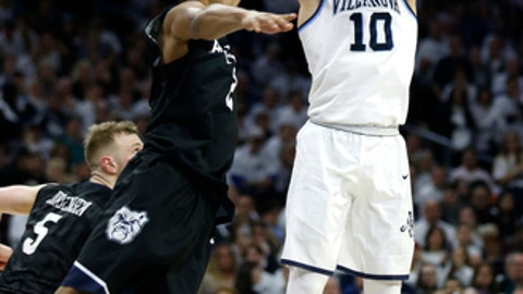 Villanova guard Donte DiVincenzo (10) takes a 3-point shot over Butler guard Aaron Thompson (2) during the final minutes in the second half of an NCAA college basketball game, Saturday, Feb. 10, 2018, in Philadelphia. Villanova won 86-75. (AP Photo/Laurence Kesterson)