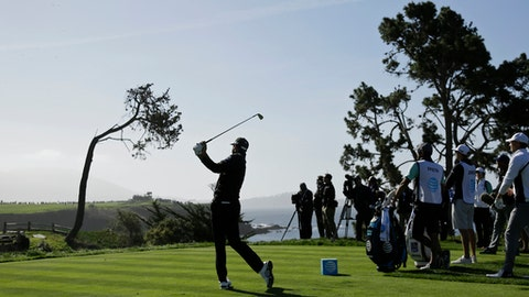 Dustin Johnson hits from the fifth tee of the Pebble Beach Golf Links during the third round of the AT&T Pebble Beach National Pro-Am golf tournament Saturday, Feb. 10, 2018, in Pebble Beach, Calif. (AP Photo/Eric Risberg)