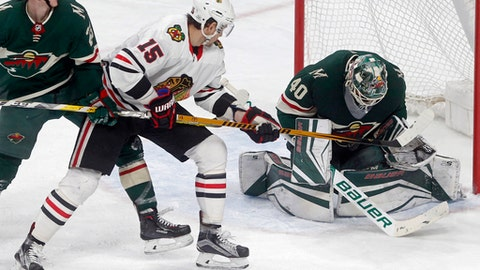 Minnesota Wild goalie Devan Dubnyk, right, stops a shot as Chicago Blackhawks' Artem Anisimov, center, closes in during the third period of an NHL hockey game, Saturday, Feb. 10, 2018, in St. Paul, Minn. The Wild won 3-0. (AP Photo/Jim Mone)